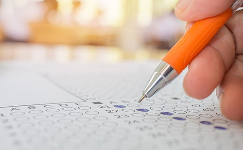Students hand testing doing examination with pen drawing selected choice on answer sheets in school exams, blur pupils college backgroud. Education system tests concept.